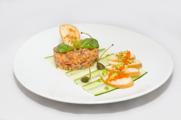 Salmon tartare on a white plate with green leaves