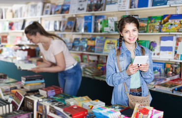 Schoolgirl with screen tablet at books store