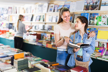 glad woman showing open book to happy girl in book boutique