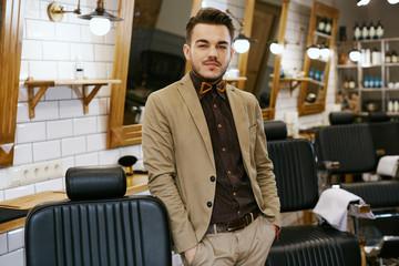 Portrait of handsome man at barbershop background