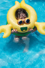 young girl in yellow crab float in sunny pool