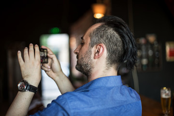 Young bearded man taking photos with his mobile phone in the bar