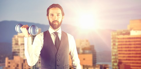 Composite image of portrait of businessman holding dumbbell