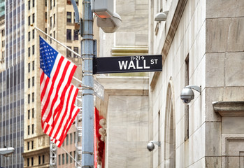 Wall Street sign with American flag in distance, shallow depth of field, New York City, USA