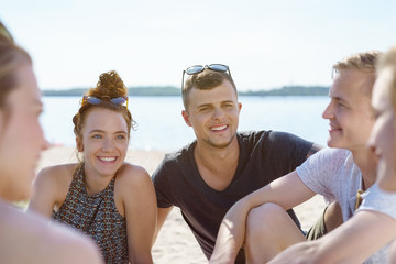 Group of young students chatting at the beach