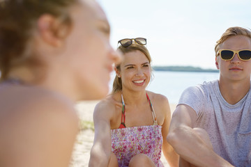 Couple sitting relaxing with friends on a beach