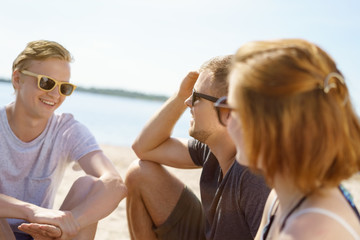 Handsome young men on a beach wearing sunglasses