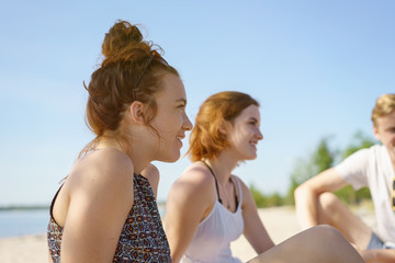 Two young women relaxing with a group of friends