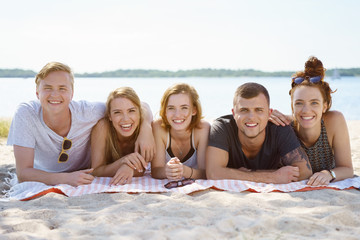 Group of young students relaxing on a sandy beach