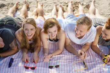 Laughing vivacious young group of friends lying on the beach
