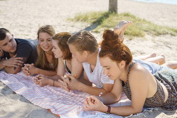 Group of young friends relaxing on a sandy beach