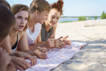 Group of young friends enjoying a quiet chat on a beach