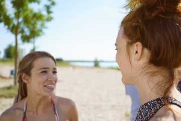 Young woman on the beach sharing a joke with her friend