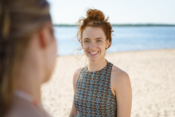 Young woman chatting with her friend on the beach