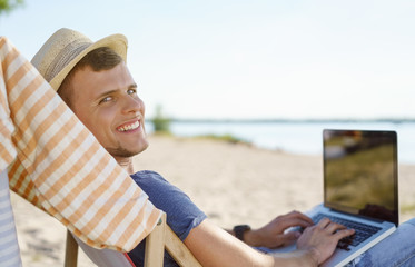 Attractive young man relaxing at the beach with laptop