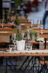 wooden table in  restaurant outdoor with wine glasses and water