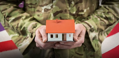 Composite image of mid section of soldier holding model home