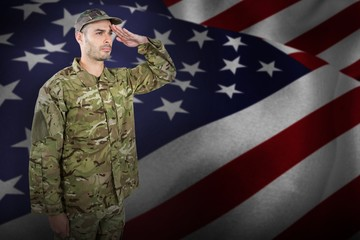 Composite image of confident military soldier saluting