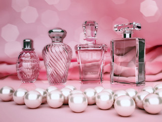 Pearls and different bottles of perfume on pink background.