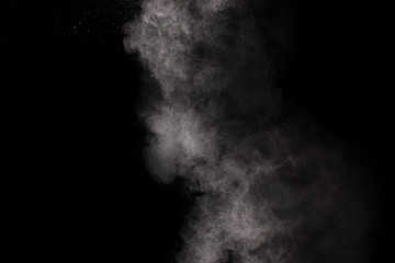 hrowing talcum powder out of hand. Stopping the movement of white powder on dark background.