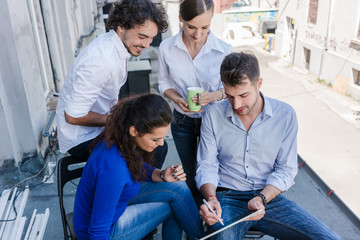 Creative business people having staff meeting outdoors of office in summer