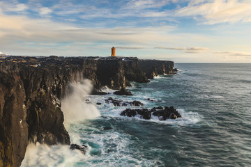 Lighthouse over the cliff, ocean seashore in Iceland