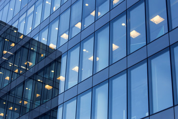 office building windows with inner artificial lamplight in blue color tone
