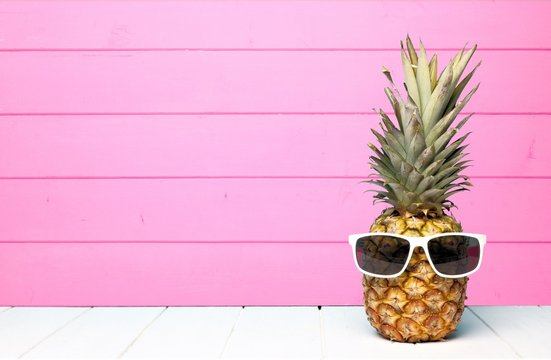Hipster pineapple with sunglasses against a pink wooden background