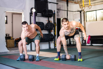 Muscular men are doing exercise