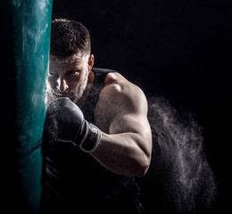 Studio shot of male boxer punching a boxing bag.