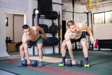 Two strong man are doing cross fit workout