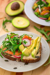 Homemade sandwich with avocado, salmon, arugula and humus. Rustic style. Gray stone background. Close-up. Top view