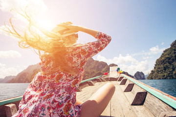 Beautiful girl traveling by boat in mountain tropical lake, the wind fluttering hair. Summer Travel concept, Thailand, Cheow lan lake
