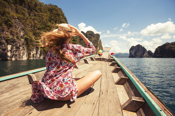 Beautiful girl traveling by boat in mountain tropical lake, the wind fluttering hair