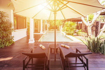 Chaise lounge, umbrella and private swimming pool near luxury villa hotel. Sunny summer holiday