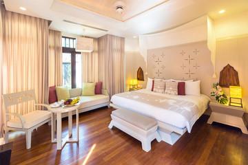 Luxury bedroom hotel interior, big window, sofa, wooden floor