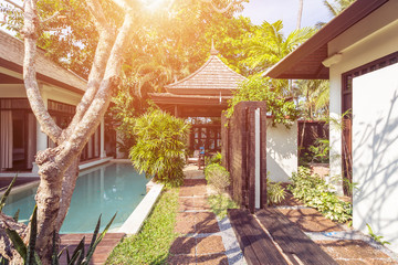 Tropical trees and private swimming pool near luxury villa hotel. Sunny summer travel vacation