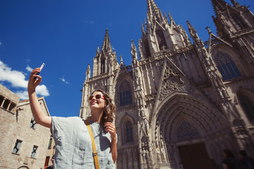 Young and happy tourist woman making selfie photo in front of cathedral in Barcelona