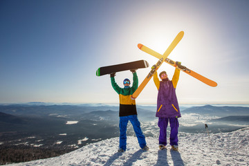 Skier and snowboarder on mountain top. Sunny winter day, active sport holiday