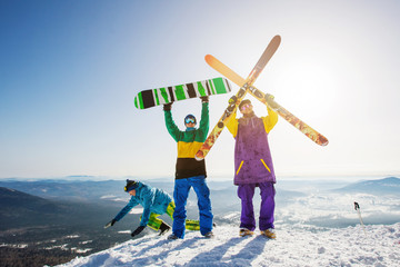 Happy Skier and snowboarder friends standing on mountain top with ski and snowboard in hands