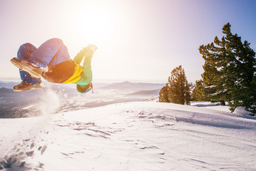 Snowboarder acrobatic guy jumping somersault on snow mountain top. Winter sport outdoor