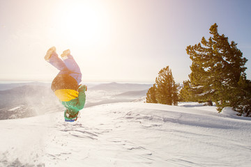Snowboarder jumping somersault on snow mountain top. Winter sport outdoor