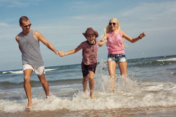 Happy young family having fun running on beach. Family traveling concept