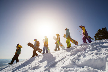 Group of people snowboarders and skiers on mountain sunset. Winter Sport outdoor