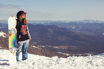 Female snowboarder standing with snowboard in her hands and preparing for ride, snowboarding concept