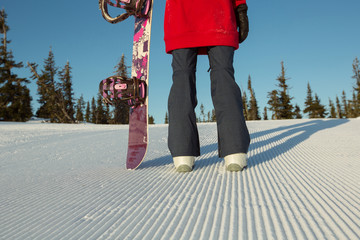 Snowboarder stands on Snow surface groomed and prepared for alpine skiing. Closeup legs and snowboard