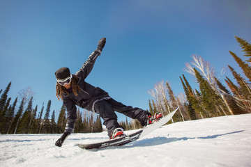 Snowboarder in sportswear doing balance trick. Beautiful mountains and forest on background