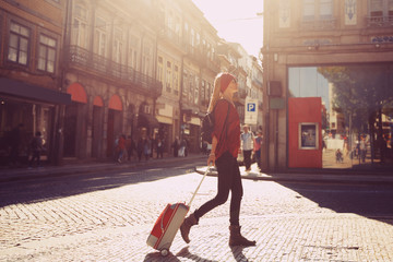 Woman tourist walking with suitcase on  European city street, tourism in Europe, travel background