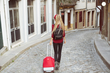 Traveling female walking with suitcase on  European city street, tourism in Europe, travel background