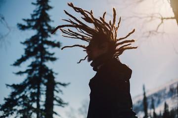 Happy man silhouette with windy dreadlocks in winter mountain forest
